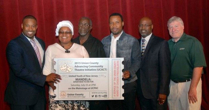 Union County Freeholder Chairman Mohamed S. Jalloh (left) presented the United Youth of New Jersey community theatre company with a Union County Advancing Community Theatre (UCACT) grant during a reception at the Union County Performing Arts Center in Rahway. He was joined by County Manager Alfred Faella (right). (Photo by Jim Lowney/County of Union)