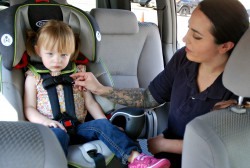 Union County child safety seat inspection technician Cristallina Tharaldsen demonstrates the proper harness fit and location of the harness clip for a forward-facing car-seat with 2-year old county resident Eleanor Wilson-Newbury during a free inspection event sponsored by the Union County Board of Chosen Freeholders. (Photo credit: Jim Lowney/County of Union).